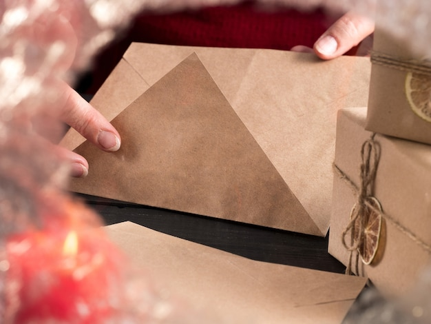 Kobieta w czerwonym swetrze wkłada list do koperty za zamarzniętym szkłem.