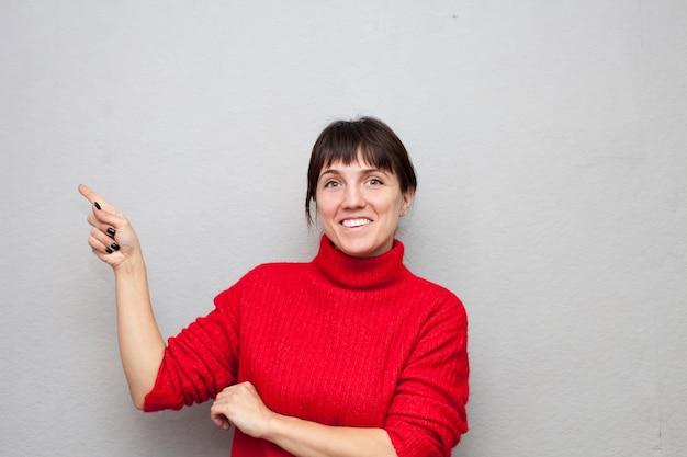 Kobieta w czerwonym swetrze wskazuje bok na szarej ścianie