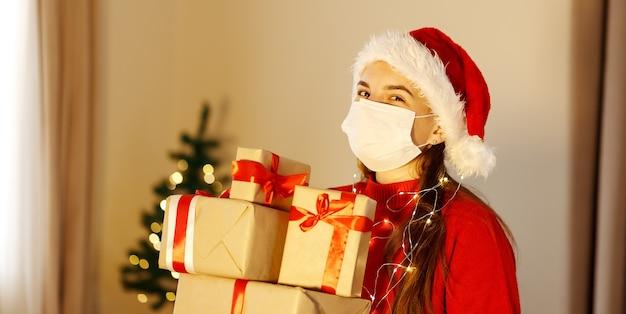 Kobieta w czerwonym swetrzemedyczna maska kapelusz z wieloma świątecznymi pudełkami prezentowymi po świątecznych zakupach
