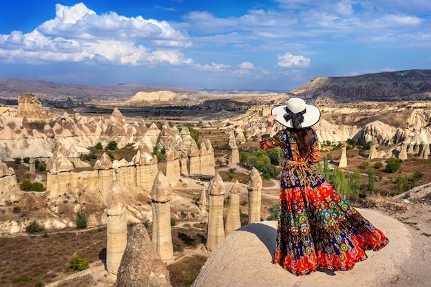 Kobieta w czeskiej sukni stojąca w dolinie miłości w kapadocji w turcji.