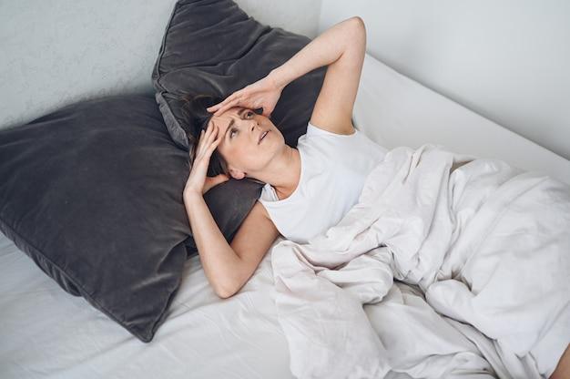 Kobieta w depresji dręczona niespokojnym snem, jest wyczerpana i cierpi na bezsenność, złe sny lub koszmary senne, problemy psychiczne. niewygodne niewygodne łóżko lub materac. brak snu