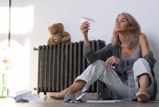 Kobieta w depresji siedzi na podłodze swojego mieszkania i patrzy na trzymany w dłoni papierowy samolot
