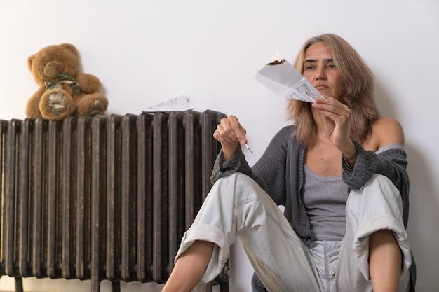 Kobieta w depresji siedzi na podłodze swojego mieszkania, podpalając papierowy samolot i obserwując, jak pali się