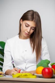 Kobieta w dietetyce w białym fartuchu pisze program zdrowej diety na odchudzanie