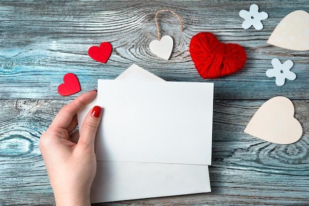 Kobieta w dłoni trzyma pusty list na romantycznym tle.