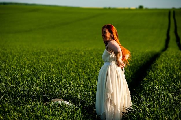 Kobieta w długiej białej sukni na zielonym polu