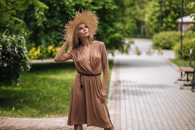 Kobieta w długiej brązowej sukience i słomkowym kapeluszu spaceruje po letnim parku