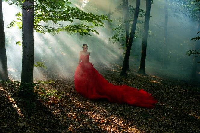 Kobieta w długiej czerwonej sukience i królewskiej koronie w mglistym lesie