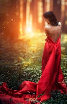 Kobieta w długiej czerwonej sukience sama w lesie