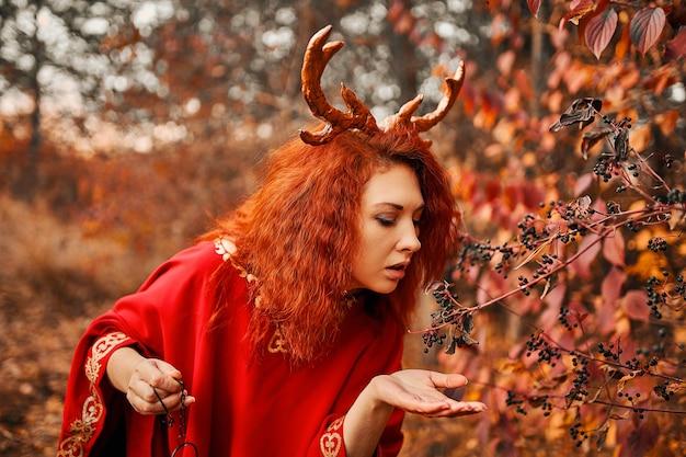 Kobieta w długiej czerwonej sukience z rogami jelenia w jesiennym lesie piękna tajemnicza gotycka stwór...