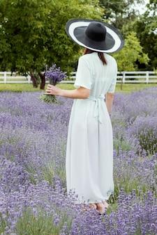 Kobieta w długiej oliwkowej sukni i kapeluszu w lawendowym polu pani z bukietem lawendy