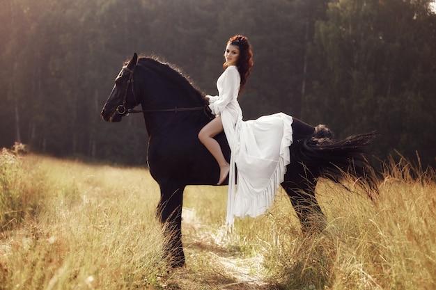 Kobieta w długiej sukni na koniu, piękna kobieta na koniu w polu jesienią. wiejskie życie i moda, szlachetny rumak