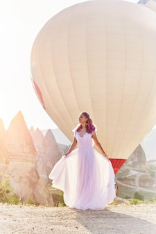 Kobieta w długiej sukni obok balonów na ogrzane powietrze w kapadocji. dziewczyna z kwiatami ręce stoi na wzgórzu i patrzy na dużą liczbę latających balonów
