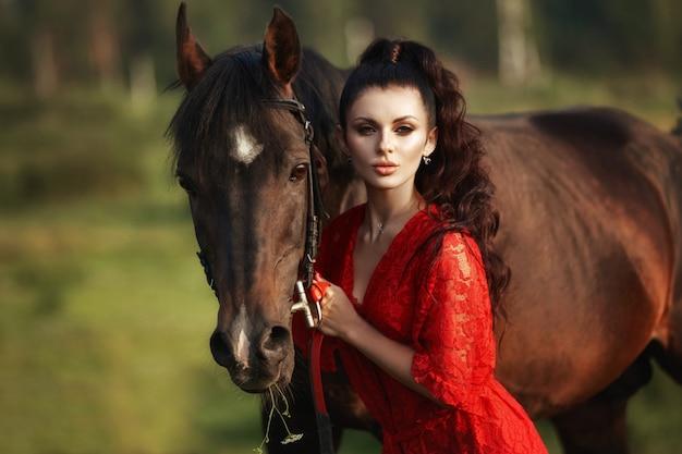 Kobieta w długiej sukni stoi w pobliżu konia, piękna kobieta głaszcze konia i trzyma uzdę na polu jesienią. wiejskie życie i moda, szlachetny rumak