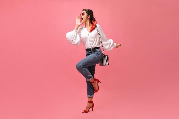 Kobieta w dobrym nastroju krzyczy na różowym tle. stylowa dziewczyna w białej bluzce, dżinsach i czerwonych szpilkach pozuje z pasiastą torebką.