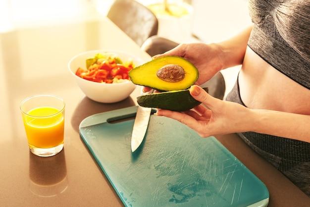 Kobieta w domowej kuchni kroi awokado dla zdrowego odżywiania