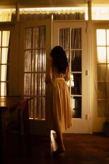 Kobieta w domu, a wokół niej tajemnicze światła dzienne