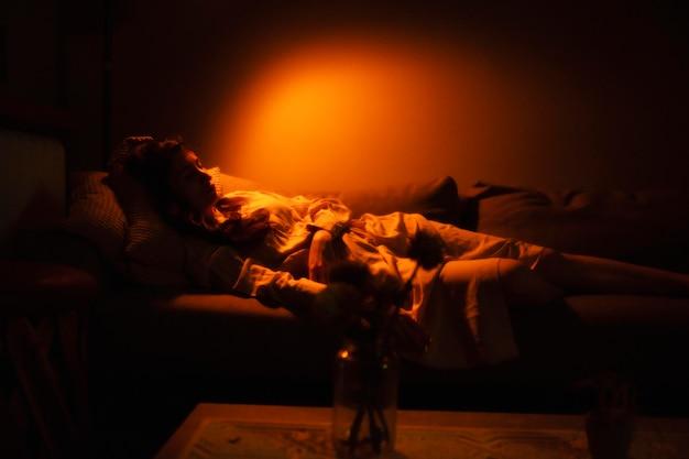 Kobieta w domu, a wokół niej tajemnicze światła wewnętrzne