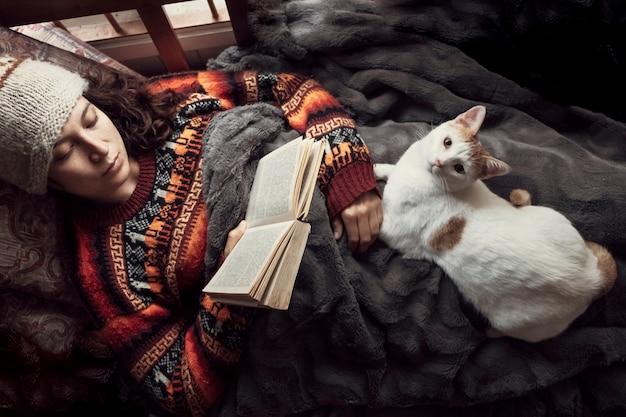 Kobieta w domu czyta starą książkę z kotem. pojęcie hobby i przebywanie w domu