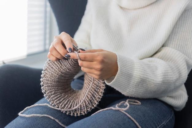 Kobieta w domu na drutach z bliska