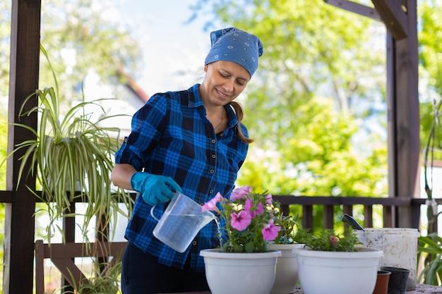 Kobieta w domu na poddaszu rośliny piękne kwiaty w doniczkach. dba o rośliny. zmienia ziemię. podlewanie kwiatów.