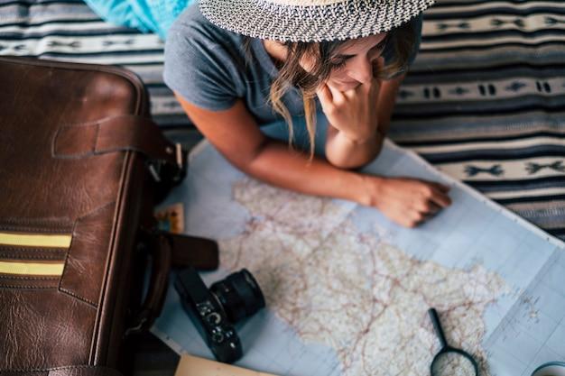 Kobieta w domu planowania podróży wakacje patrząc na mapę przewodnika i uśmiech