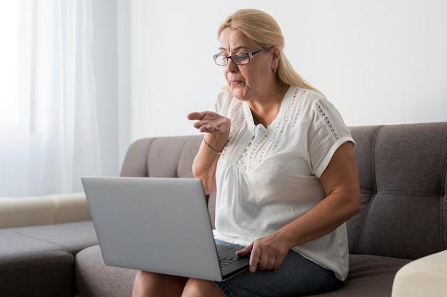 Kobieta w domu poddana kwarantannie podczas rozmowy wideo z przyjaciółmi