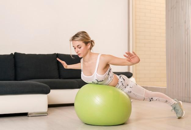 Kobieta w domu pracuje nad piłką fitness
