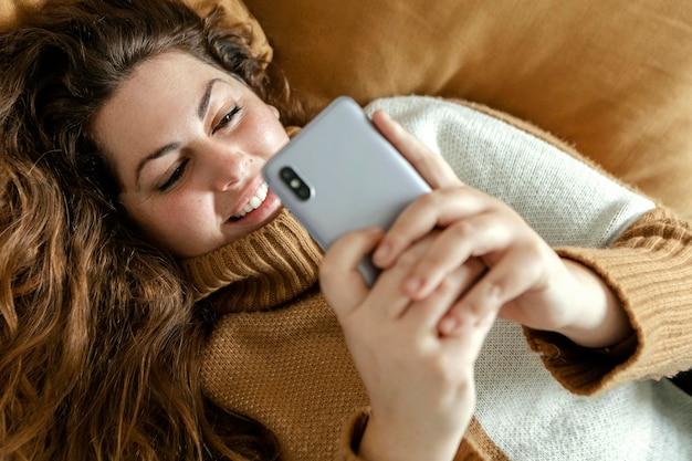 Kobieta w domu przy użyciu telefonu komórkowego