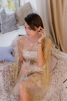 Kobieta w domu przytulny pokój ubrany w błyszczącą świąteczną suknię wieczorową, trzymając kieliszek szampana