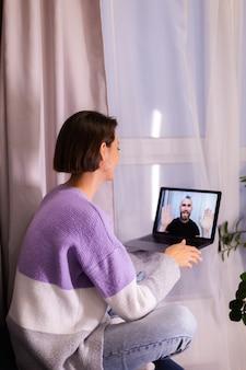 Kobieta w domu rozmowa wideo twarzą w twarz z jej przyjacielem mężem chłopakiem, rozmawiając online z laptopa