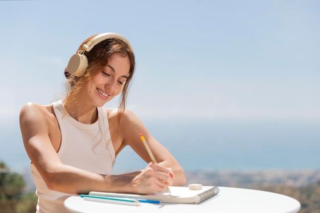 Kobieta w domu, słuchanie muzyki i rysowanie