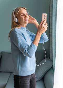 Kobieta w domu, słuchanie muzyki na słuchawkach ze smartfonem podczas pandemii