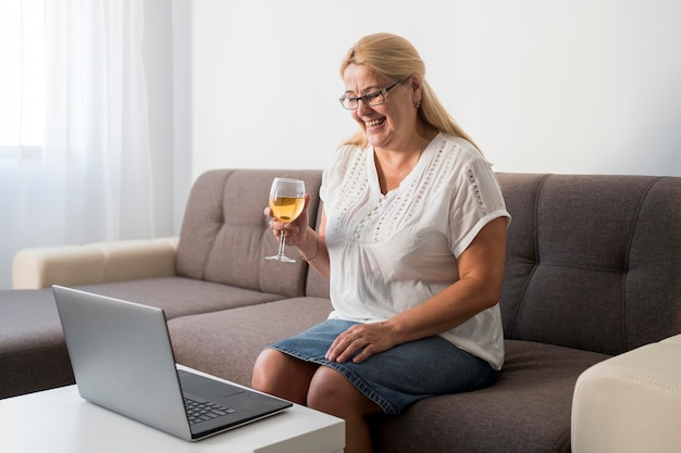Kobieta w domu w kwarantannie po rozmowie wideo na laptopie z napojem