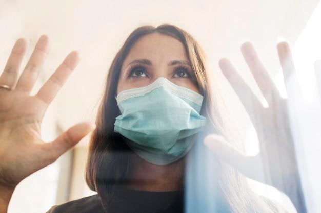 Kobieta w domu w kwarantannie z maską medyczną za oknem