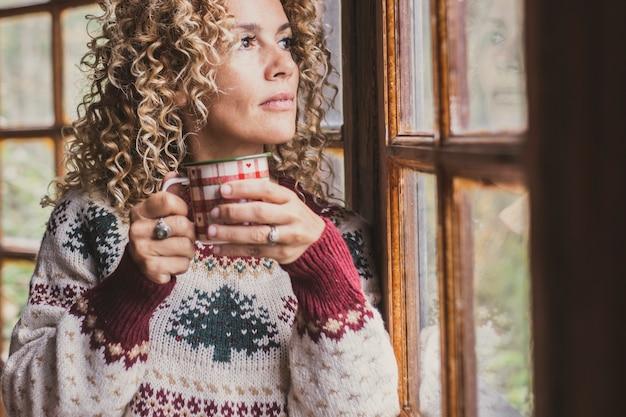 Kobieta w domu wygląda na zewnątrz i pije kawę ze świątecznego kubka