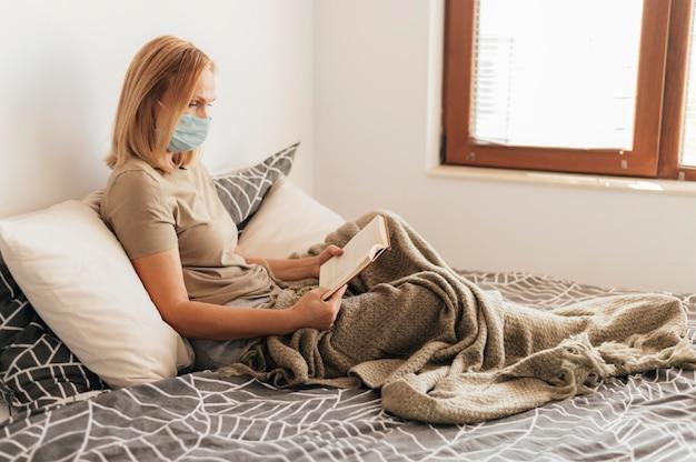 Kobieta w domu z medyczną maską i książką