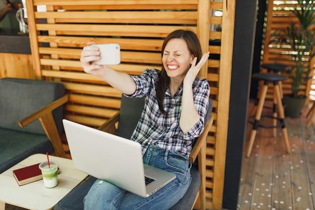 Kobieta w drewnianej kawiarni na zewnątrz ulicy lato siedzi z laptopa komputer pc, robi selfie strzał na telefon komórkowy, relaks w czasie wolnym. biuro mobilne