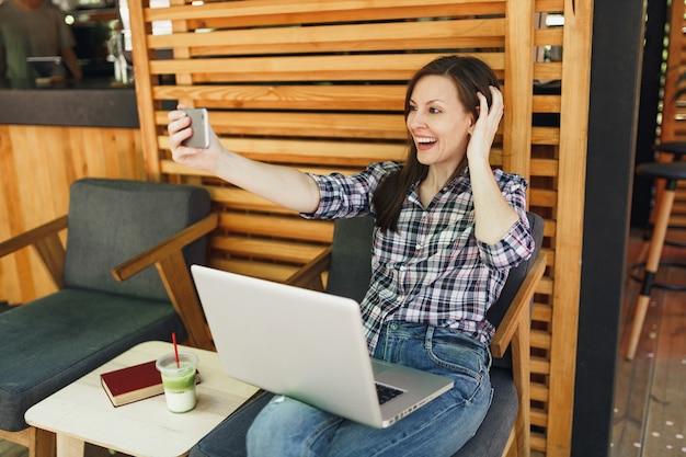 Kobieta w drewnianej kawiarni na zewnątrz ulicy letniej siedzi z komputerem przenośnym, robi selfie na telefonie komórkowym
