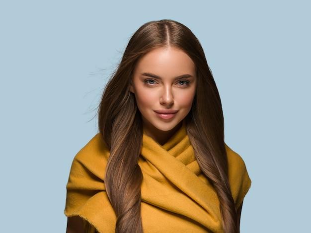 Kobieta w dzianiny ubrania żółty jesień zima styl długie włosy. kolor tła niebieski