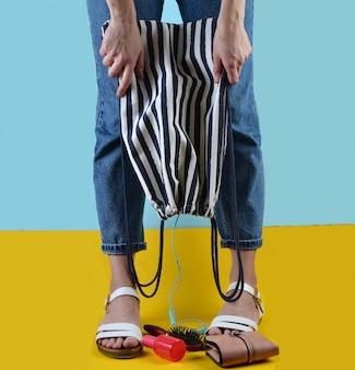 Kobieta w dżinsach i sandałach trzyma plażową pasiastą torbę na niebiesko żółtej ścianie. akcesoria damskie wypadają z torby. co jest w damskiej torbie? czas letni w nadmorskim kurorcie