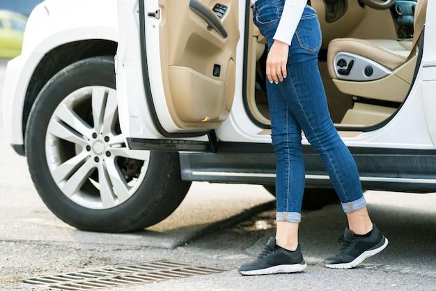 Kobieta w dżinsach i trampkach stojąca w pobliżu dużego samochodu terenowego na zewnątrz. kierowca dziewczyna w przypadkowych ubraniach poza jej pojazdem.