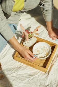 Kobieta w dżinsach siedzi na łóżku i je zdrową miskę muesli podczas porannego słońca, śniadanie w łóżku.