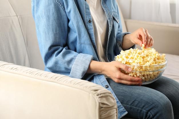 Kobieta w dżinsowej koszuli ogląda film na kanapie i je popcorn