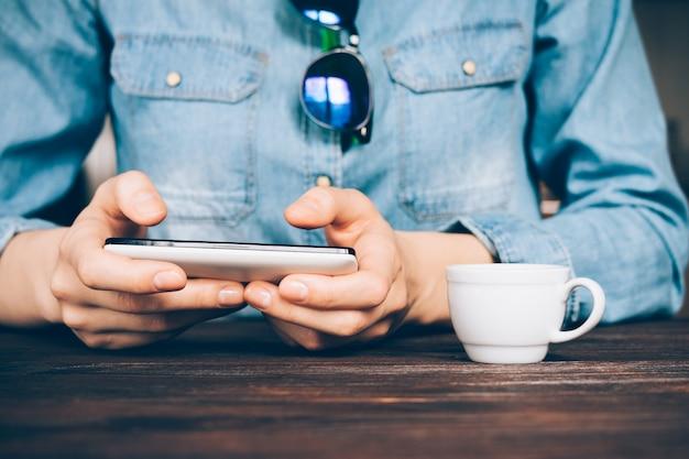 Kobieta w dżinsowej koszuli używa telefonu komórkowego w kawiarni