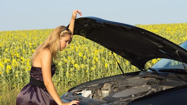 Kobieta w eleganckiej sukience zaglądająca pod podniesioną maskę swojego pojazdu, próbująca ustalić przyczynę awarii