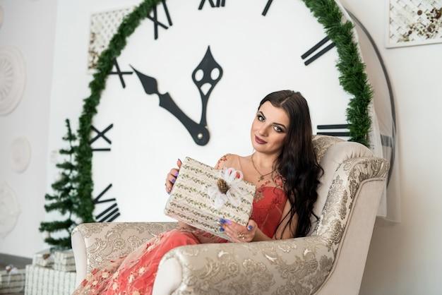 Kobieta w eleganckiej sukni siedzi na krześle z pudełkiem prezentowym