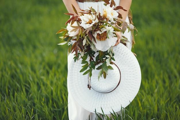 Kobieta w eleganckiej sukni stojącej w letnim polu