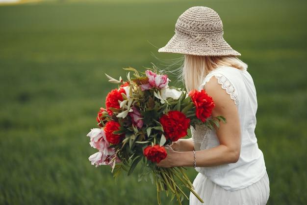Kobieta w eleganckiej sukni stojącej w polu lato