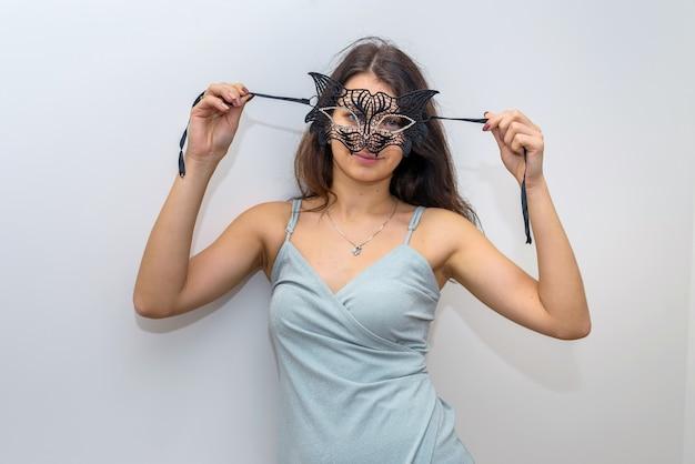 Kobieta w eleganckiej sukni wieczorowej przygotowuje się do maskarady, trzymając maskę. obchody nowego roku